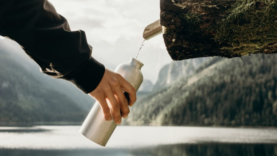aluminum water bottle getting water from a natural source