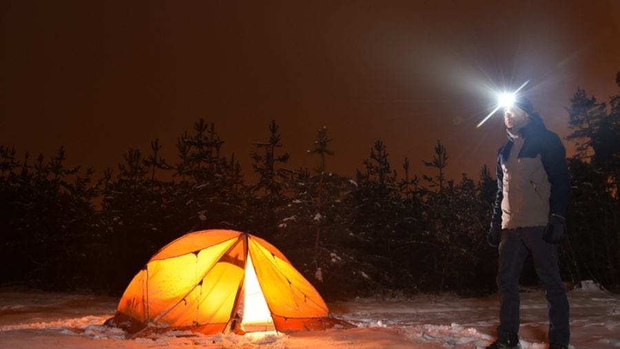 camper with headlamp on a snowy night