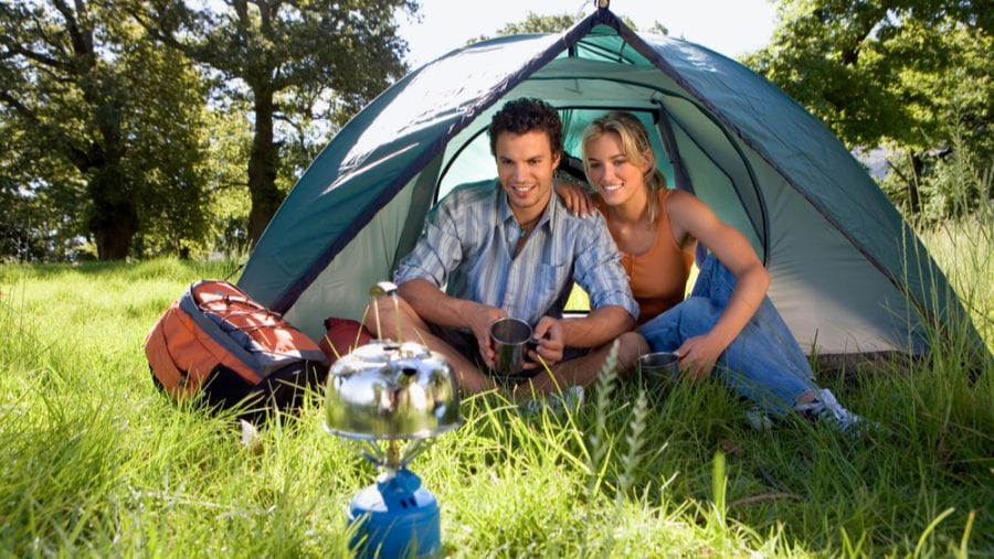 couple heating up water on a camping stove