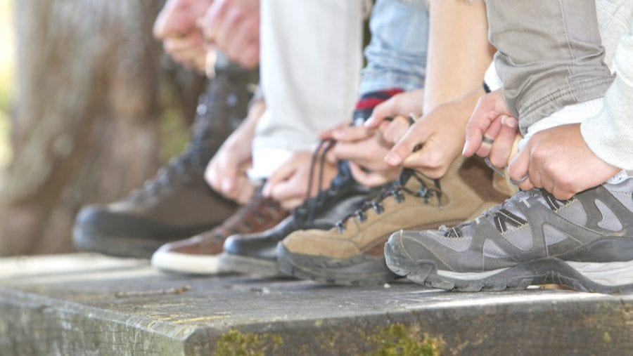 family tying laces of hiking boots