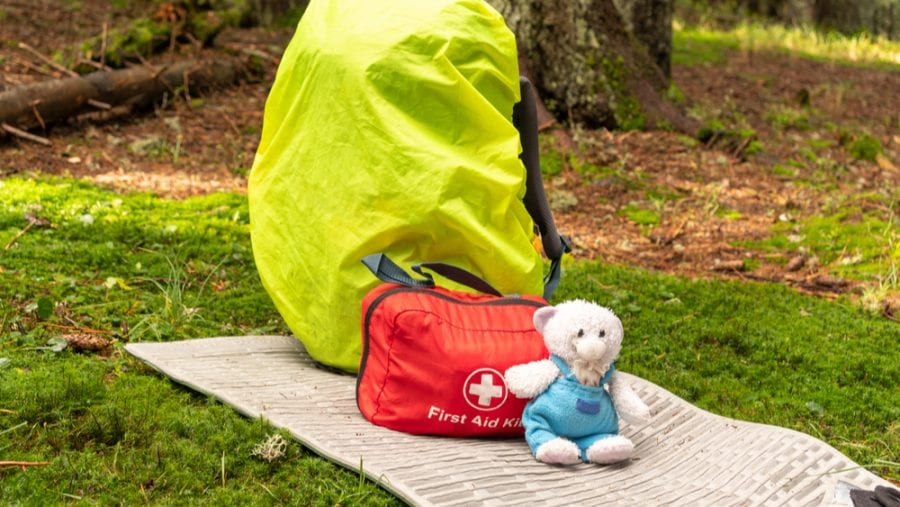 first aid kit sitting next to a hiking backpack