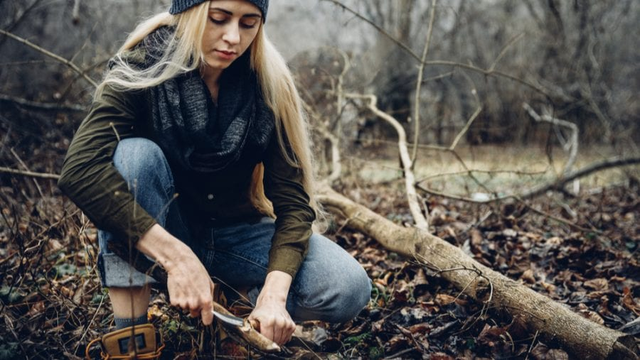 hiker cutting wood with knife