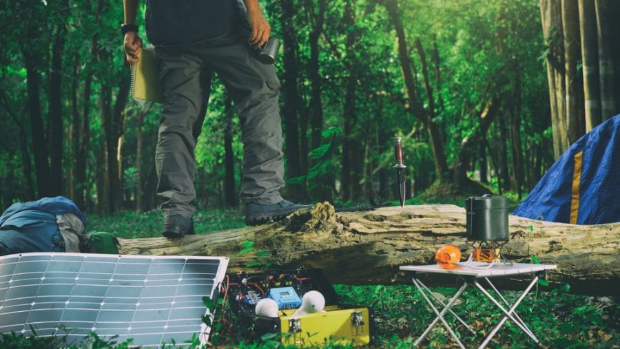 man enjoying a quiet time with a portable electric solar generator hybrid while camping