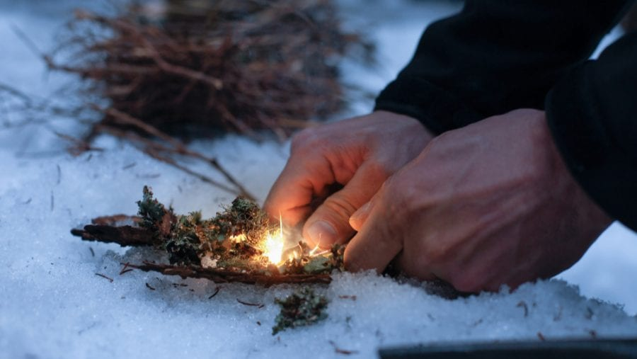 man setting up fire with a firestarter on snowy surface