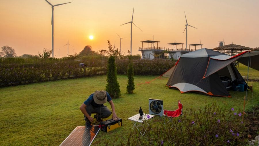 man setting up his portable generator and solar panel