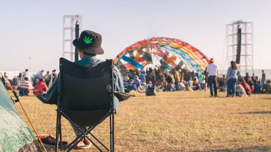 man sitting on a camping chair at a festival