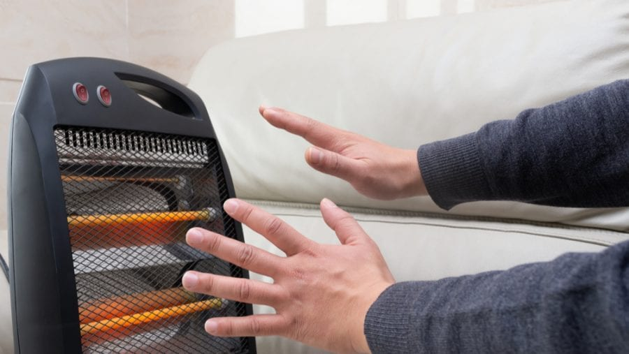 man warming up his hands on a portable electric heater