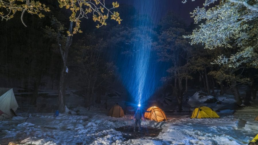 man with a headlamp at a winter camping ground