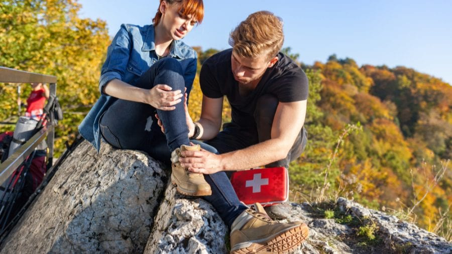 man with first aid kit helping woman