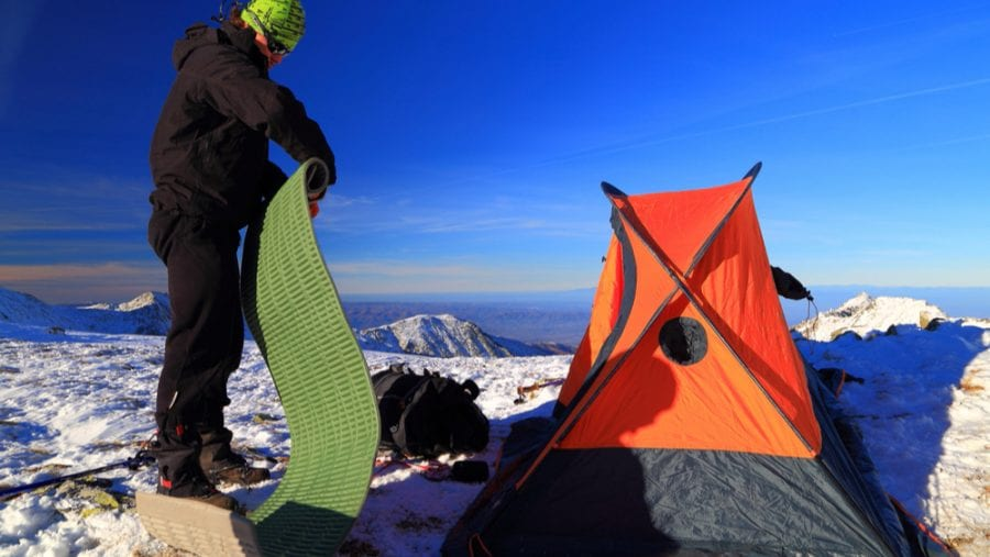 man with green sleeping pad during winter camp