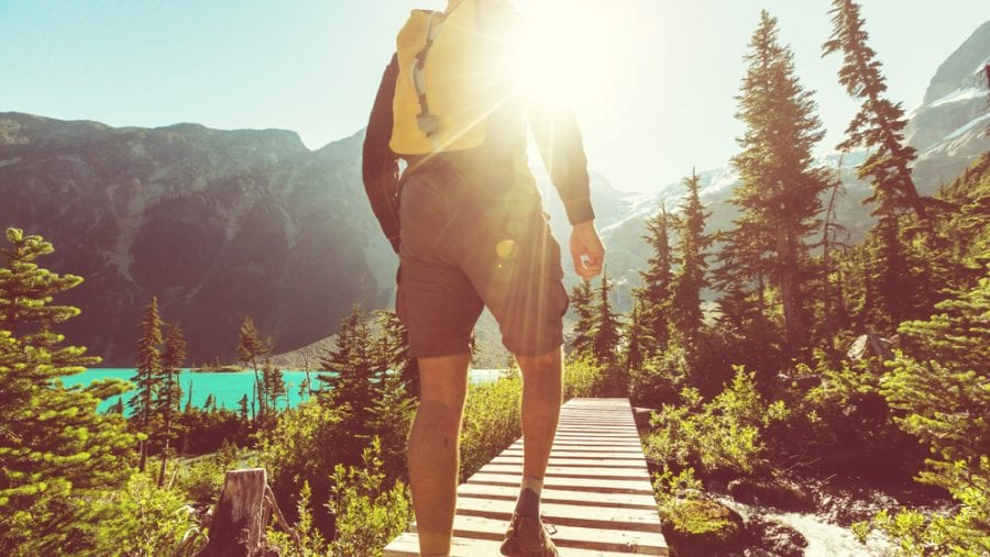 man with yellow hiking backpack in summer