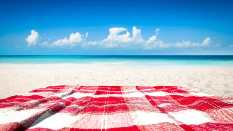 red and white blanket on a white beach