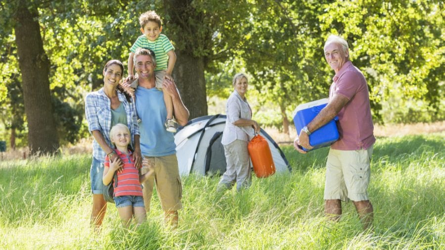 senior carrying blue camping cooler with family