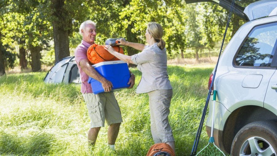 senior couple with blue camping cooler