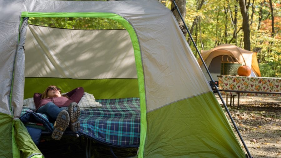 woman relaxing in tent on a cot