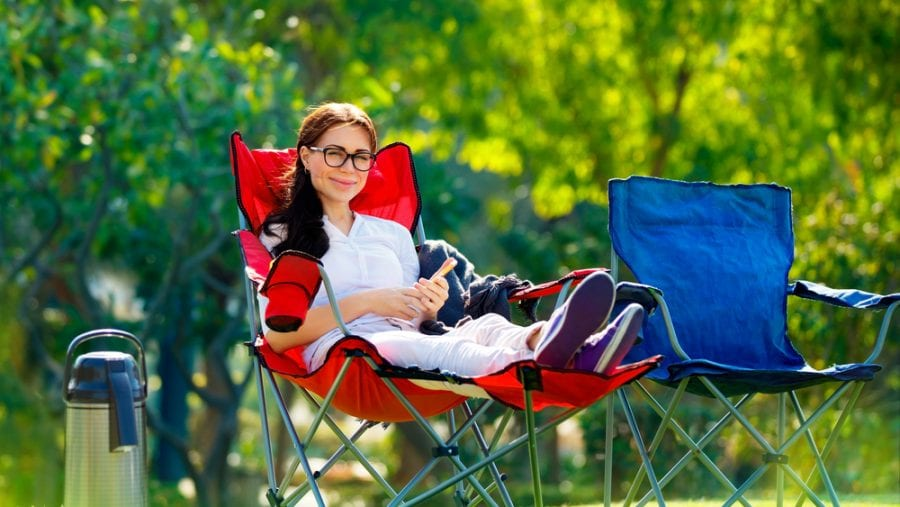 woman sitting on red camping chair