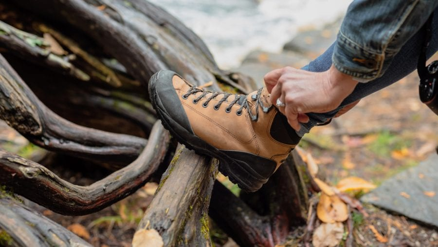 woman tying up the laces of her hiking boots outdoor
