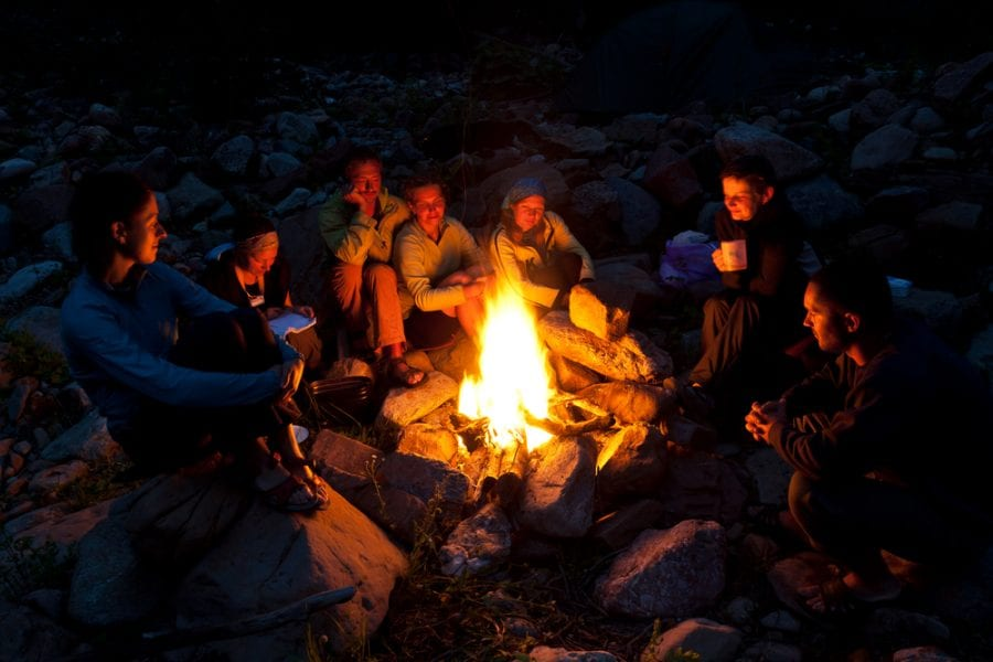 Adults chatting around a campfire
