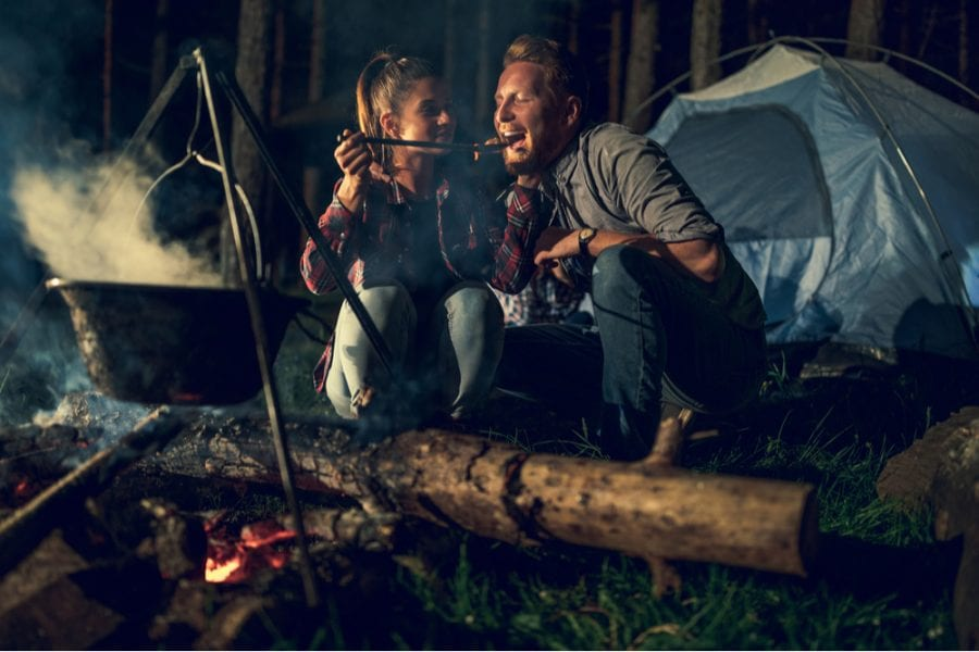 Couple cooking a romantic camping dinner