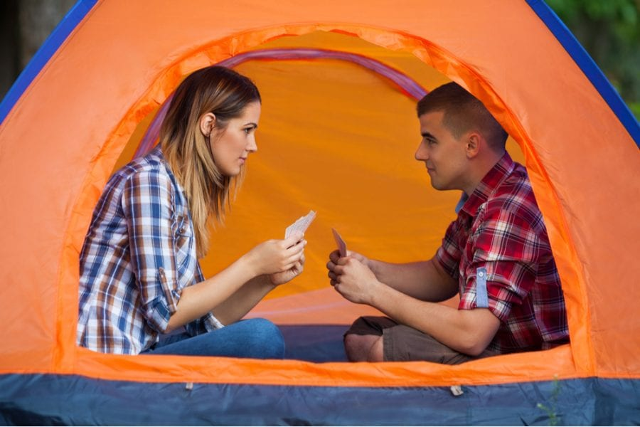 Couple playing card games in a tent