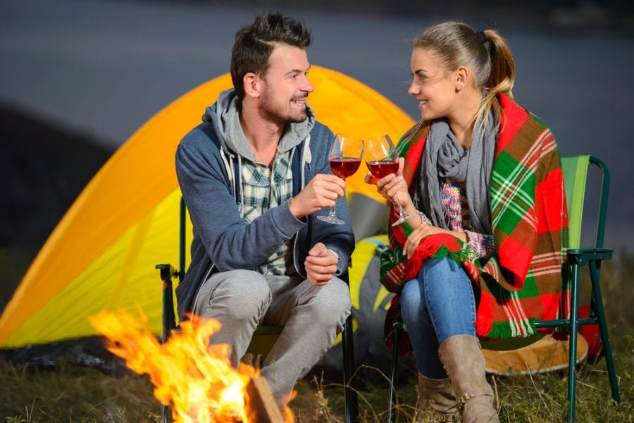 Romantic couple near a fire while camping and drinking wine