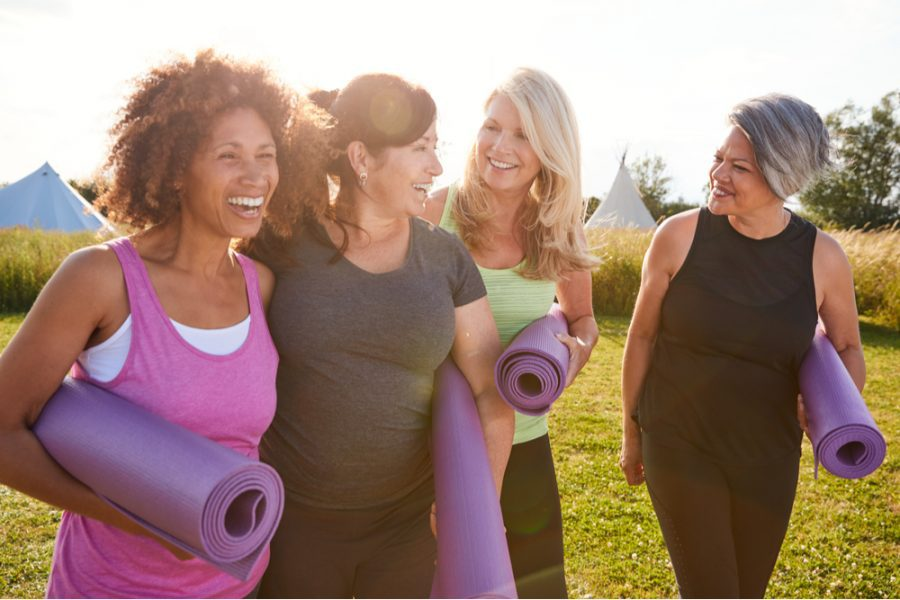 group of mature women happily talking and walking along the campsite