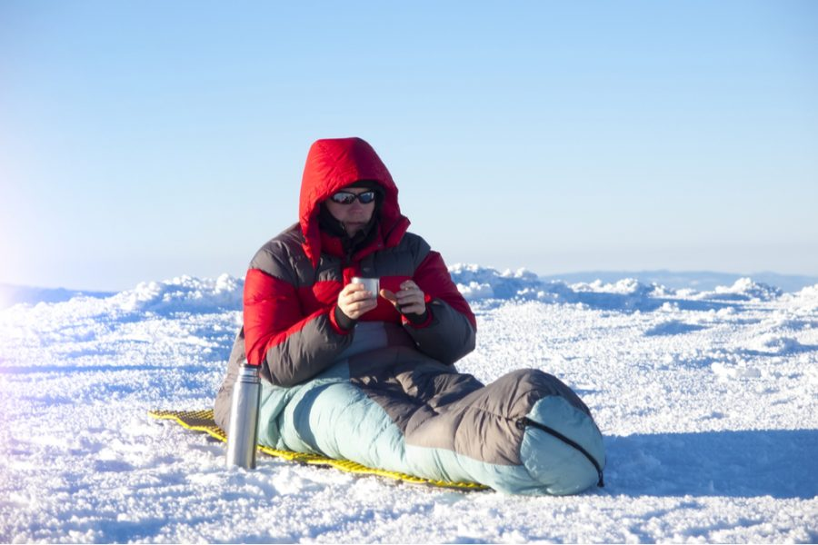 man sitting on a sleeping bag drinking hot coffee from a thermos
