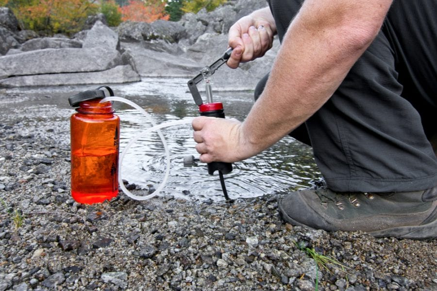 man pumping water using a compact water filter